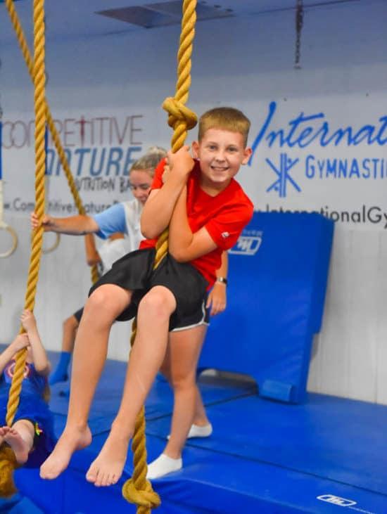 Boy swinging on rope in class