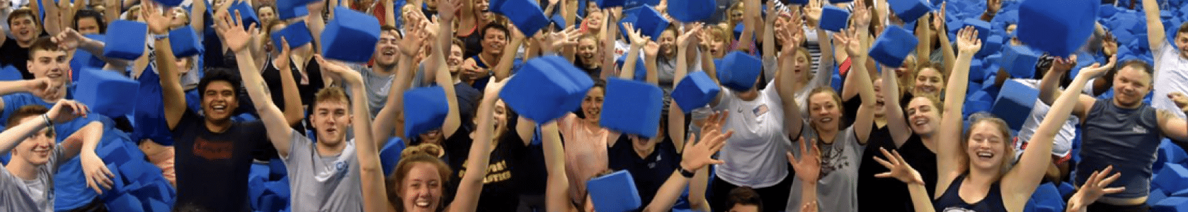 Coaches throwing foam blocks in the air for group photo