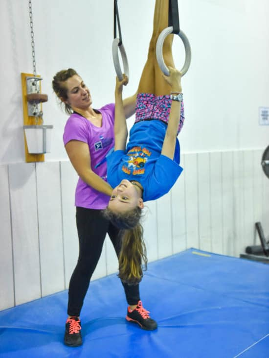 Coach helping girl upside down on the rings