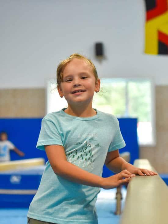 Girl smiling while walking next to balance beam