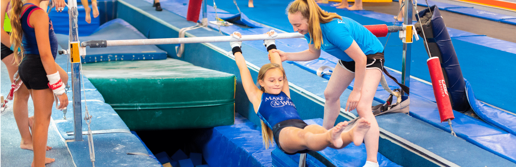 Girl swinging on bar with coach helping