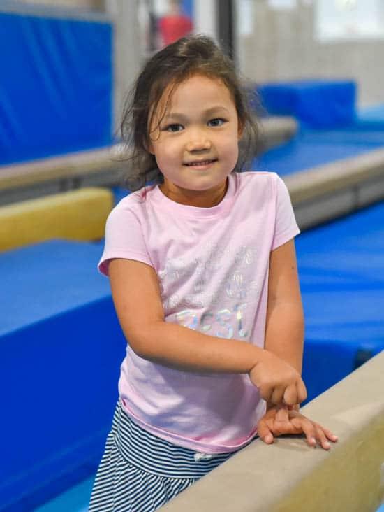 Girl smiling next to balance beam