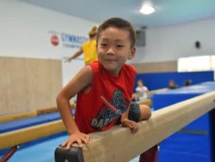 Boy getting on the balance beam