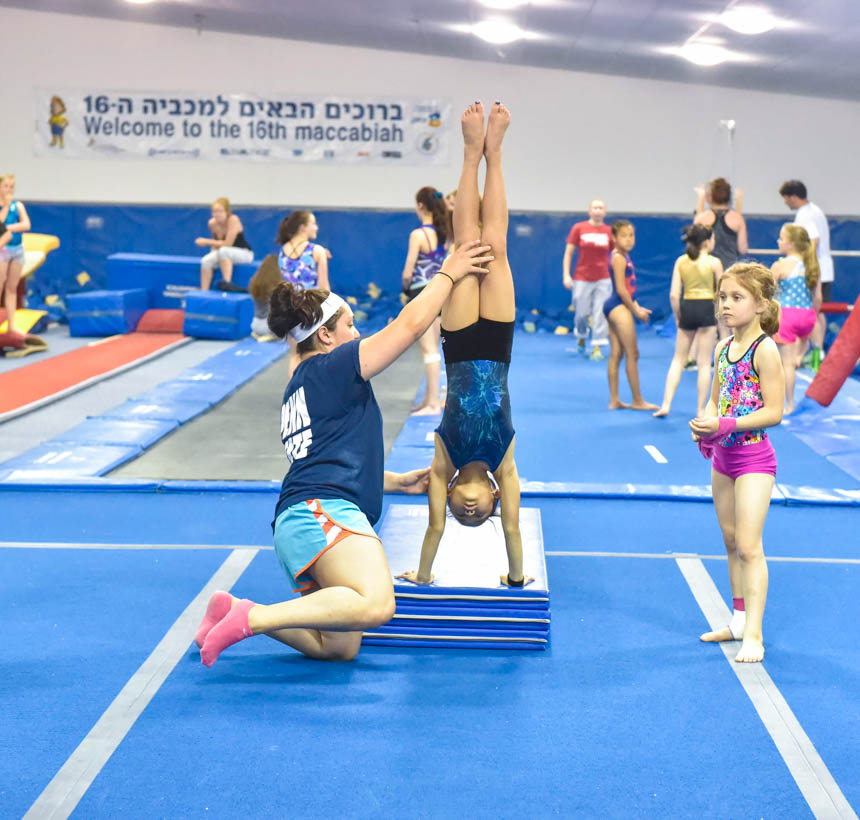 Coach helping a girl do a handstand