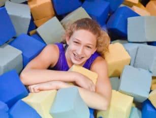Girl in a pile of foam cubes
