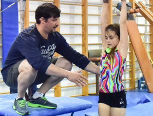 Coach helping girl on the bars
