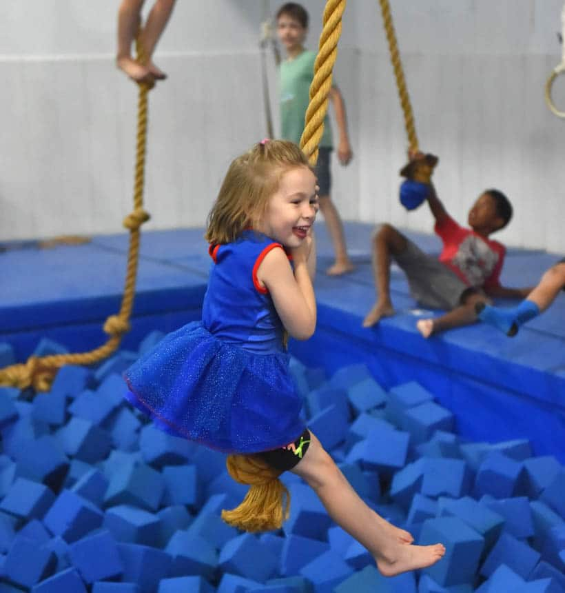 Young girl swinging on a rope